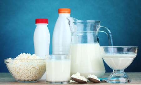 leche y derivados: Productos l�cteos en la mesa de madera sobre fondo azul