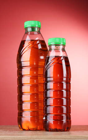 Bottles with juice on red background photo