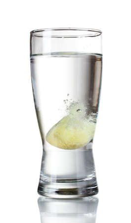 effervescence: Glass with tablet in water with bubbles isolated on white