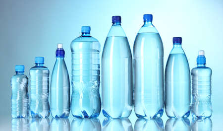 Group plastic bottles of water on blue background photo