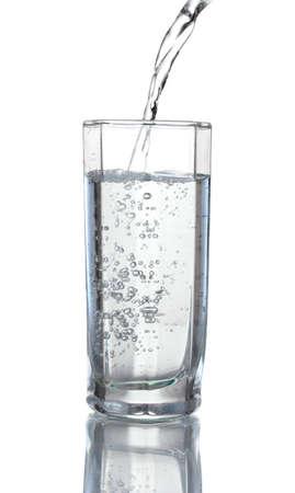 vaso con agua: Verter agua sobre vidrio aislado en blanco