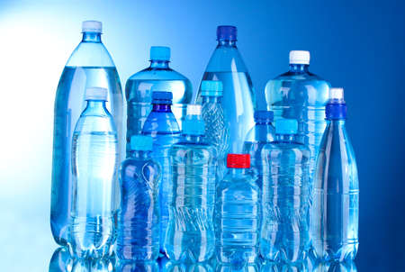 hydrate: Group plastic bottles of water on blue background