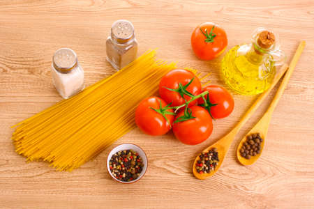 Pasta spaghetti with tomatoes, olive oil, peper  and basil on a wooden background photo