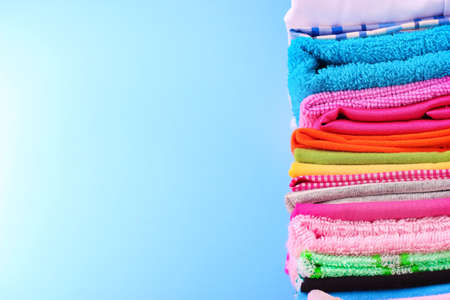clean clothes: Pile of colorful clothes over blue background