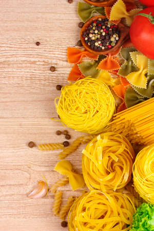 different pasta and spices on wooden background Stock Photo - 10534653