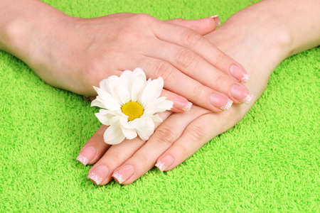 Beautiful hand with perfect nail french manicure  on towel background photo