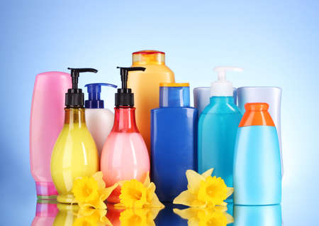 personal hygiene: bottles of health and beauty products on blue background with reflection