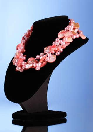 perle rose: rose collier de perles et de coquillages sur un fond bleu Banque d'images