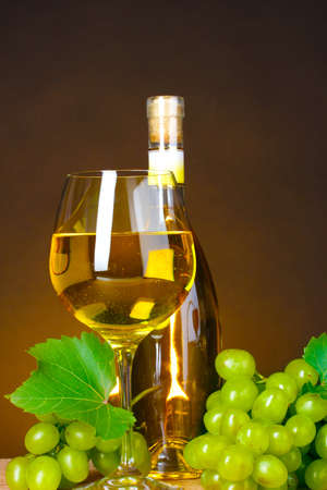 Glass of wine,bottle and grapes on yellow background photo