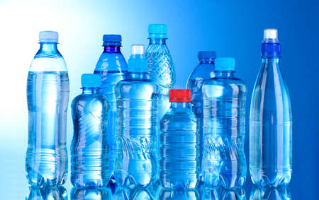 Bottiglie di plastica gruppo di acqua su sfondo blu Archivio Fotografico