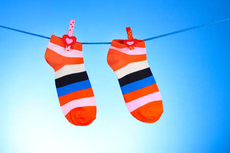 Bright striped socks on line on blue background photo