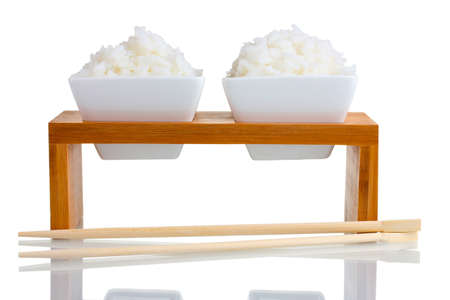 Two bowls on wooden stand of cooked rice and chopsticks isolated on white photo