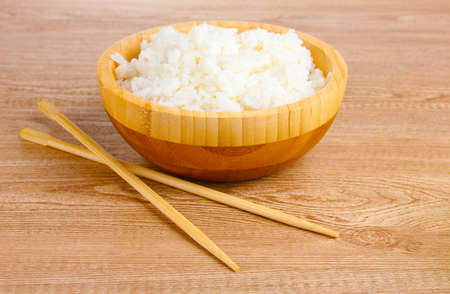 Wooden bowl of cooked rice and chopsticks on wooden table Stock Photo - 10573621