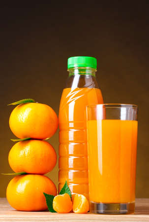 Tangerines, juice glass and bottle on wooden table on brown background Stock Photo - 10573809