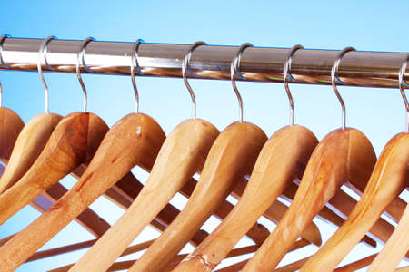 wooden clothes hangers on blue background