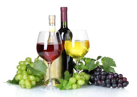 Rijpe druiven, wijn glazen en flessen wijn op wit wordt geïsoleerd Stockfoto
