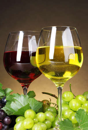 Glasses of wine and grapes on yellow background photo