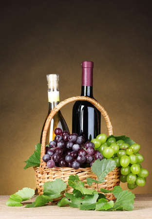 Bottles of wine and grapes in basket on yellow background photo