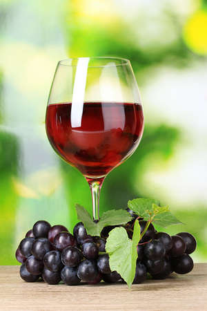 Ripe grapes and  glass of wine on  green background photo