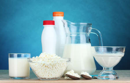 calcium: Dairy products on wooden table on blue background