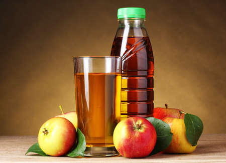 Apple juice and apples on wooden table on brown background photo