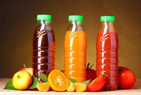 jugos: Diferentes jugos y frutas en la mesa de madera sobre fondo marr�n