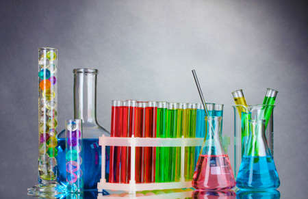 Test-tubes with liquid on gray background photo