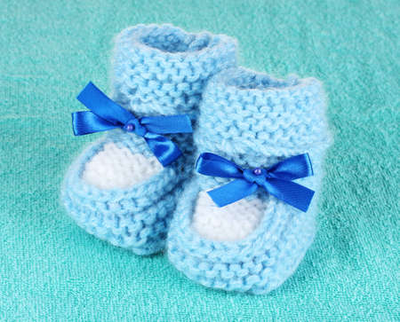 Blue baby booties on blue background photo