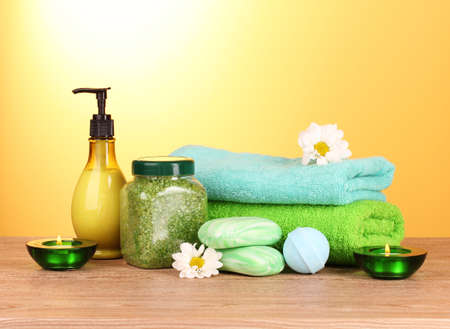 Bath salt, soap and towel on yellow background photo