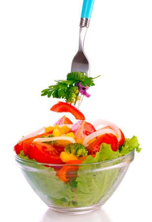 salad fork: many vegetables on the plate isolated on white