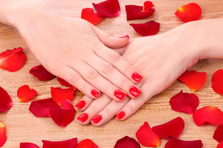 beautiful red manicure and  flower on a wooden background Stock Photo - 10670384
