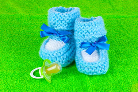 Blue baby booties and pacifier on green background photo
