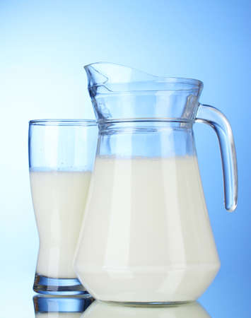 Tasty milk in jug and glass on blue background photo