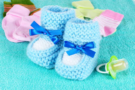 Blue baby booties, socks and pacifier on blue background photo