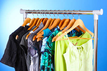 different clothes on wooden hangers on blue background photo
