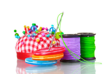 darn: Bright sewing buttons, needle and skeins of thread isolated on white