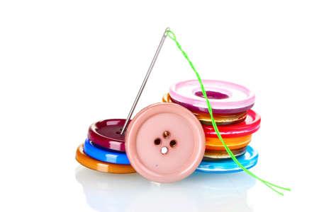 hilo rojo: Botones brillantes de coser y una aguja con hilo aislado en blanco Foto de archivo