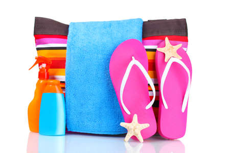 bright striped beach bag and beach items isolated on white photo