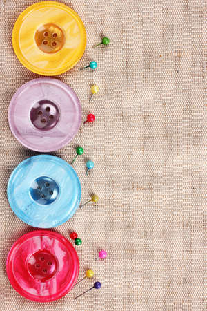 Bright sewing buttons on gray fabric photo