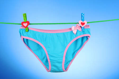 Womans panties hanging on blue background photo