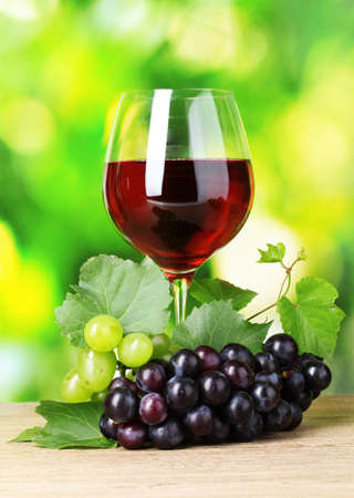 Ripe grapes and  glass of wine on  green background Stock Photo - 10774143