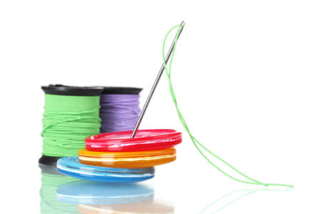 Bright sewing buttons, needle and skeins of thread isolated on white photo