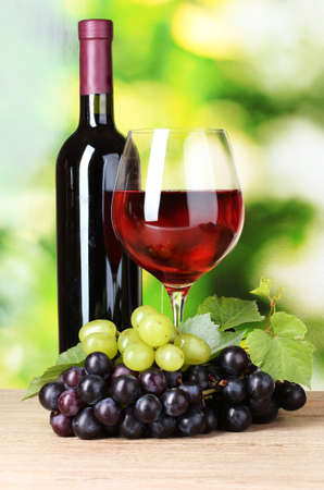 Ripe grapes and  glass of wine on  green background Stock Photo - 10822384