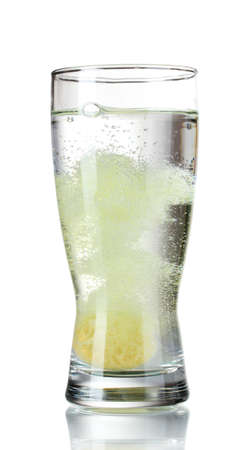 Glass with tablet in water with bubbles isolated on white photo