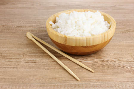 Wooden bowl of cooked rice and chopsticks on wooden table photo