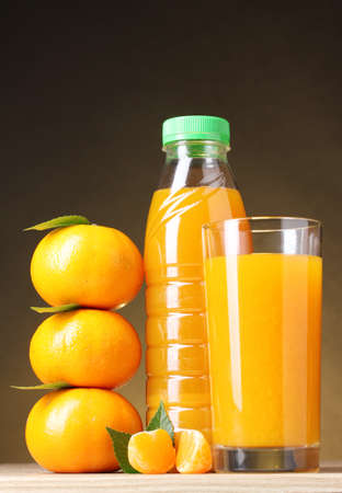 Tangerines, juice glass and bottle on wooden table on brown background photo