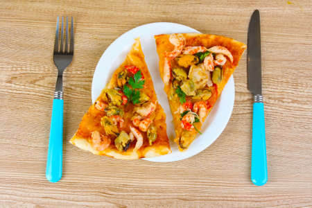 Delicious pizza with seafood on plate on wooden background photo