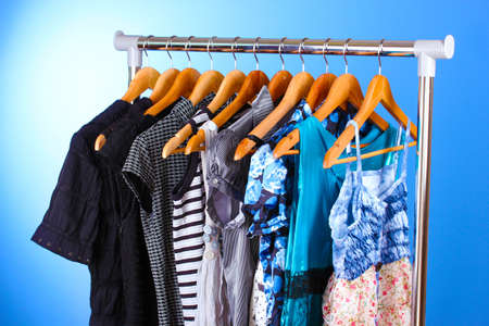 hangs: different clothes on wooden hangers on blue background