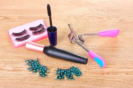 beautiful decorative eyelashes on wooden background photo