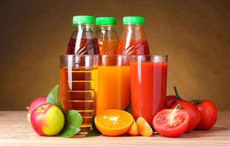 jugos: Diferentes jugos y frutas en la mesa de madera sobre fondo marrón